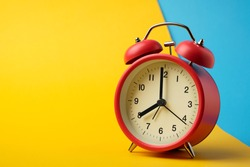 Red vinatge alarm clock show 8 o'clock with yellow and blue background.