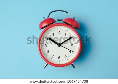 Red vintage alarm clock on light blue color background