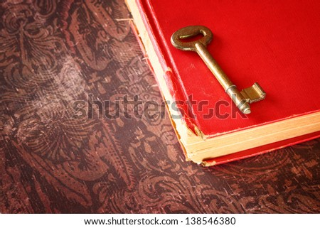 red vintage book with golden classic key on cover
