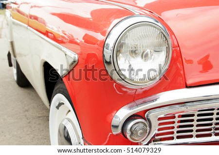 Red vintage car on a festival of old cars. Retro car's headlight close up. #514079329