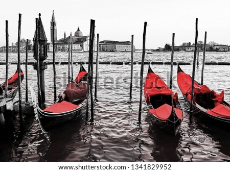 Red vintage gondolas docked at the pier the Piazza San Marco in Venice, Italy. Color in black and white