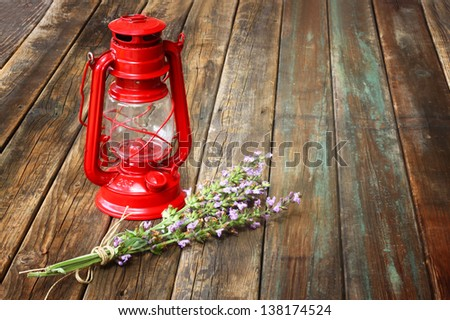 red vintage kerosene lamp, and sage flowers on wooden table. fine art concept.