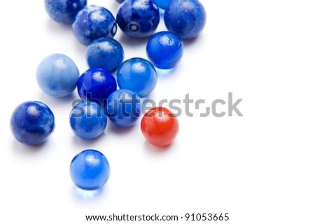 Red vintage marble standing out in a crowd of blue marbles isolated on white