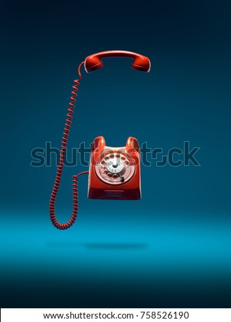 red vintage phone ringing with...