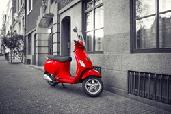 Red vintage scooter parked on sidewalk of empty city street. Black and white. Selective color effect