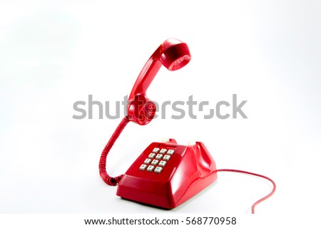 Red vintage telephone isolated on white background.