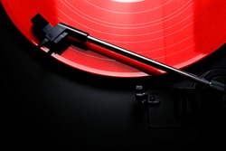 Red vinyl record spinning on a turntable - gramophone needle - directly above