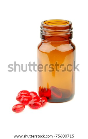 Red vitamin pills in vial isolated on white background