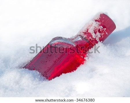 red vodka bottle in the snow