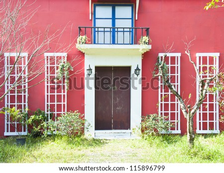 red wall brown door white glass windows