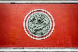 Red wall with dragon circular sculpture at the Confucian temple of Dali old town in Dali Yunnan China