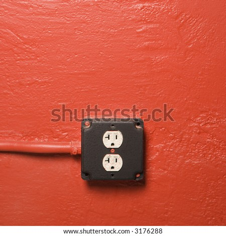 Red wall with electrical outlet.