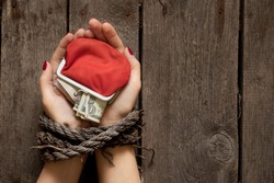 red wallet with American dollars in the girl's tied hands on the table