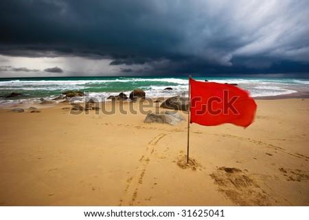Red warning flag at Surin beach. Phuket, Thailand.