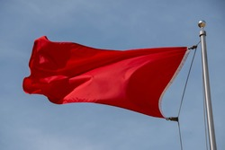 Red warning flag at the beach Red fabric cloth in blue sky. Wavy background Communist, Communism, Rebellion, Revolution