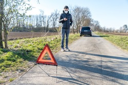 red warning triangle on the road in front of a broken car. A young man using a telephone to order assistance service