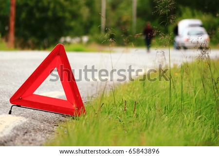 Red warning triangle with a broken down car