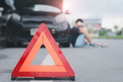 Red warning triangle with a broken down car,Emergency triangle on the road, stopped car and man calling by phone in the background.