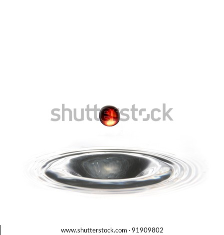 red water droplet falling into a hole of water