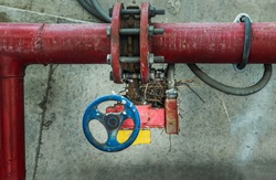 Red water or gas pipeline with gate pressure valve on concrete wall. Industrial tubes and valves, Line pipe industrial and extinguisher pump, Copy space, Selective focus.