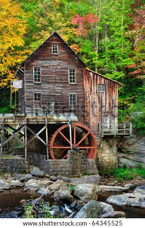 Red water wheel on old grist mill in gorgeous autumn fall colors