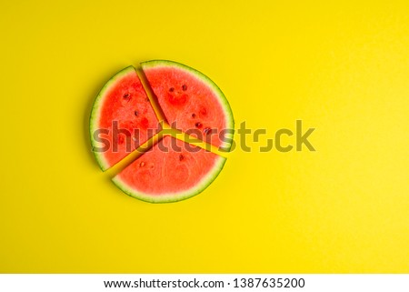 Red watermelon sliced in three portions on a yellow table. Flat lay image with copy space