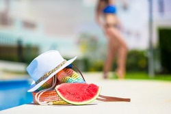 Red watermelon, straw bag and hat near swimming pool outdoor