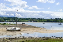 Red wharf bay, Anglesey, Wales. Beautiful landscape of sea and sand at low tide. Small pleasure boats on the sand flats. Blue sky - copy space.