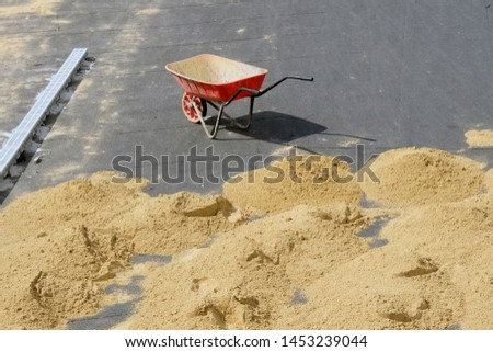 Red wheelbarrow with one wheel on the pavement and many small slides of sand on the ground. Improve road paths in the city, work outside on a hot sunny day. #1453239044