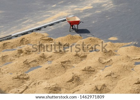 Red wheelbarrow with one wheel on the pavement and many small slides of sand on the ground. Improve road paths in the city, work outside on a hot sunny day. #1462971809