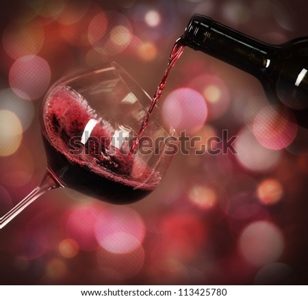 Red whine being poured in the wine cellar