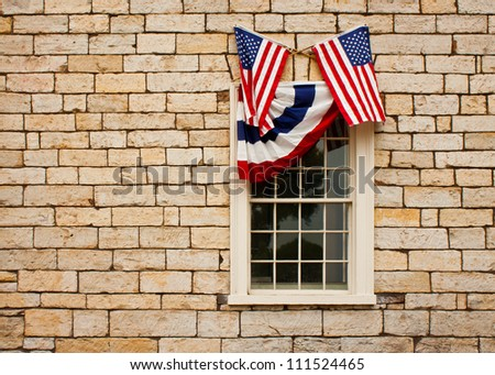 Red, white and blue bunting and crossed American flags adorn a casement style window set in a stand stone block wall.