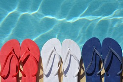Red white and blue flip flops sitting on the edge of a swimming pool.