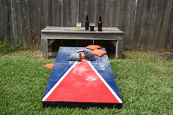 Red White and Blue home made dusty cornhole lawn game with Orange and black corn bags with beer bottles in the background