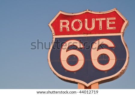 Red, white, and blue Route 66 neon sign in the shape of a US Highway shield glowing without the neon at sunset