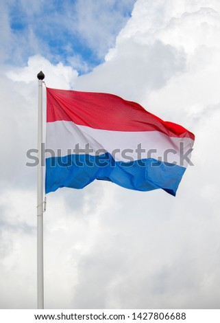 red white and blue striped dutch flag flying in front of a cloudy sky #1427806688