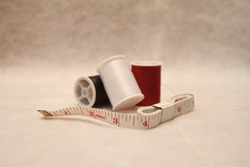 Red White and Blue Thread with A White and Red Measuring Tape on A White Background.