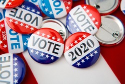 Red, white, and blue vote buttons on background with American flag, elections 2020