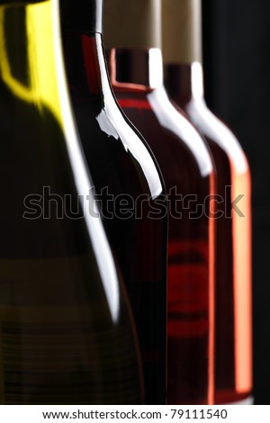 Red, white and rose wine bottles in a row
