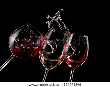 Red, white and rose wine splash on black background