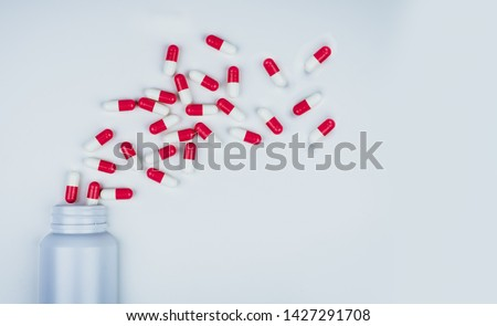 Red-white antibiotic capsule pills spread out of white plastic drug bottle. Antibiotic drug resistance concept. Antibiotic drug use. Global healthcare. Pharmacy background. Pharmaceutical industry.