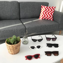 Red, white, black cateye sunglasess , on the table , glasses near the flower