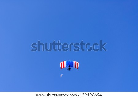 Red white & blue ultra light aircraft flying with a blue sky background.