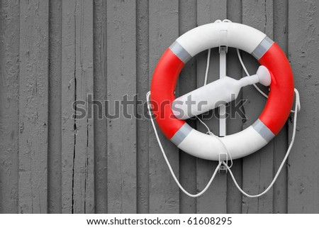 red white lifebuoy on grey wood wall