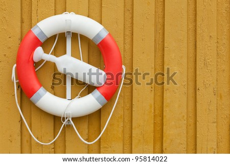 red white lifebuoy on yellow wood wall