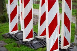 Red & white reflective roadblock barricades for directing traffic during roadwork or maintenance in a construction zone. Concept of traffic safety or road traffic.
