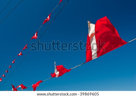 Red-white triangular ship flags flap in the breeze against a deep clear sky