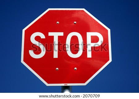 Red & White U.S. style stop sign against a deep blue sky background.