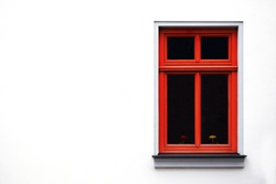 red window frame on a white wall, in the window there are flowers yellow and red
