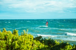 Red Windsurf on sunny day waves and trees on foreground